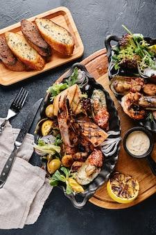 Bellissima composizione su un tavolo di pesce servito, calamari, gamberi, trancio di salmone e polpo.