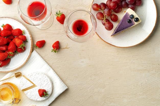 Bella composizione con cheesecake alla fragola, uva, formaggio e mirtilli