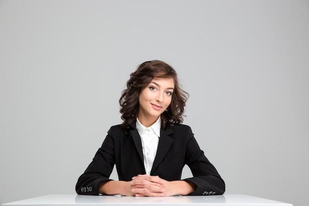 Bella donna d'affari riccia sicura di sé in giacca nera seduta e sorridente
