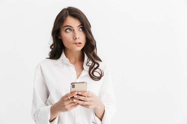 Bella giovane donna confusa con lunghi capelli castani ricci che indossa una camicia bianca in piedi isolata sul muro bianco, usando il telefono cellulare