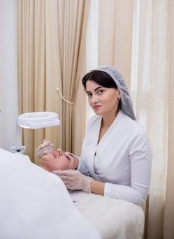 Un bellissimo cosmetologo in uniforme bianca e un berretto fa trattamenti per il viso per un cliente