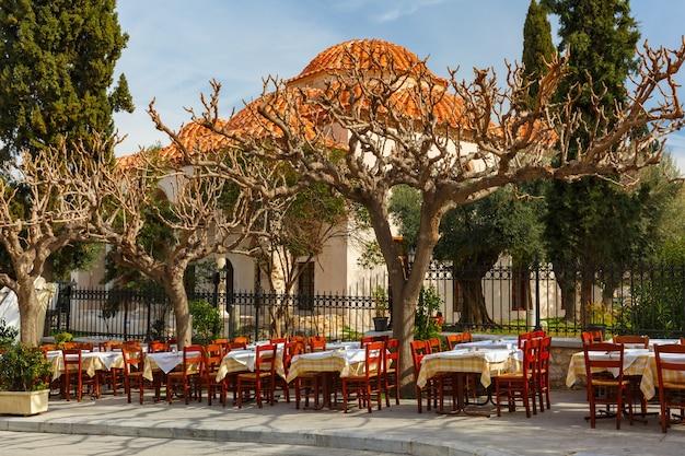 Bella strada stretta accogliente con caffè vuoto accanto alla moschea fethiye nel famoso quartiere di placa, città vecchia di atene, grecia