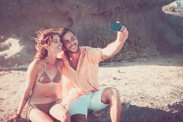 Bella coppia di adulti che prendono un selfie insieme in spiaggia seduti sugli scogli - donna in bikini sorridente e guardando la telecamera del telefono - coppia caucasica
