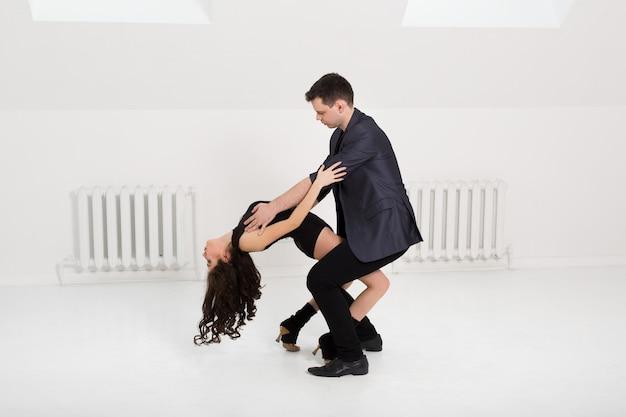 Belle coppie che ballano bachata sulla parete bianca