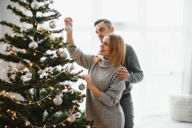 Belle coppie che decorano insieme un albero di natale