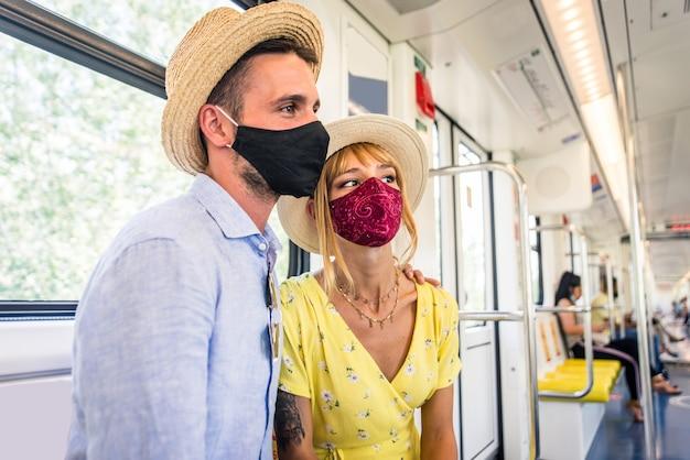 Belle coppie che guidano su un vagone della metropolitana durante la pandemia covid-19