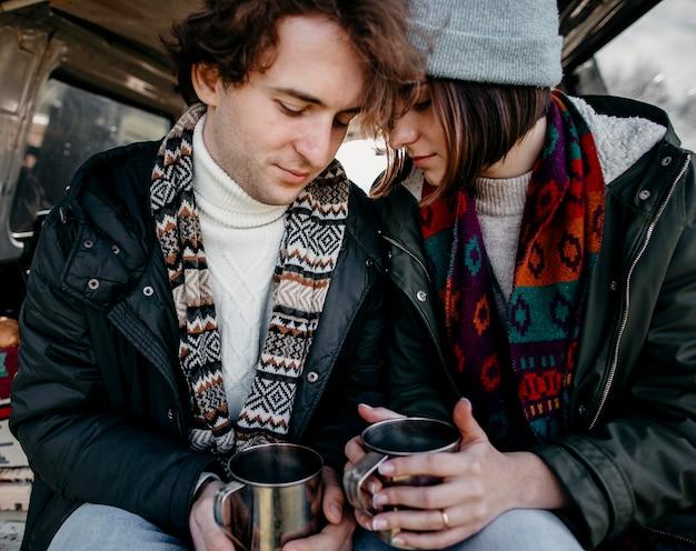 Belle coppie che tengono tazze di caffè in un furgone