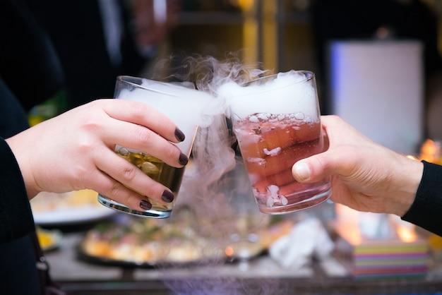 Belle coppie che tengono cocktail di ghiaccio secco alla festa.