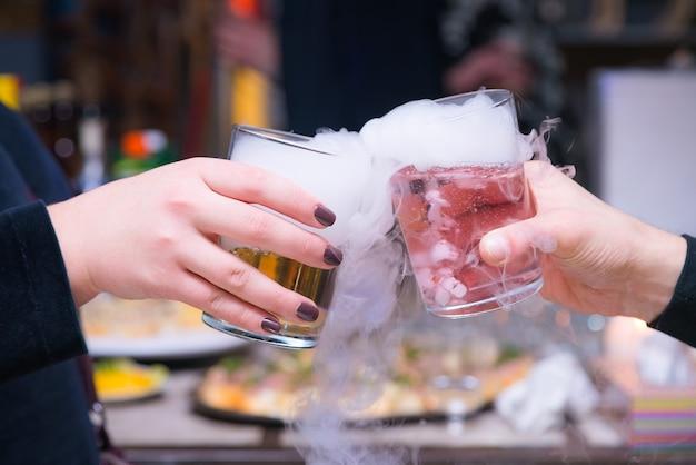 Belle coppie che tengono i cocktail di ghiaccio secco di fumo alla festa.