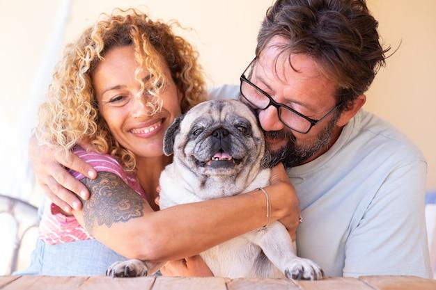 Bella coppia che si abbraccia con il loro cagnolino chiaro amici per sempre uniti e famiglia felice