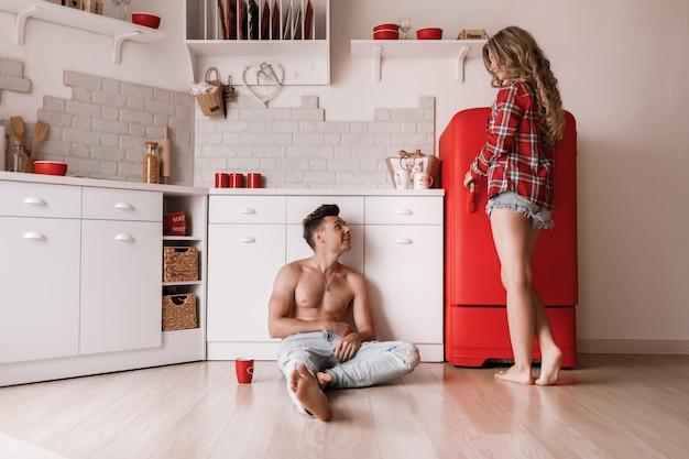 La bella coppia sta mangiando, parlando e sorridendo mentre era seduto in cucina a casa. godendo la bella mattinata insieme. messa a fuoco selettiva