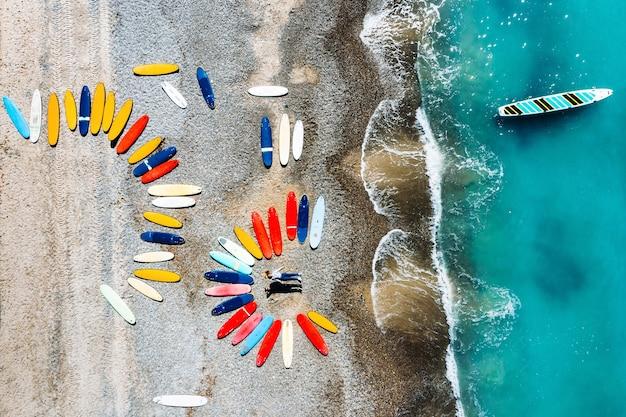 Una bella coppia è sdraiata sulla spiaggia della francia vicino alle tavole da surf, mentre riprende da un quadricottero