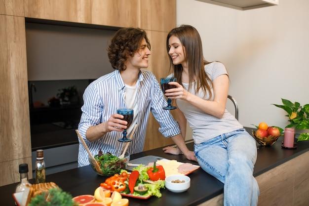 Bella coppia sorride mentre beve vino rosso e cucina insieme in cucina