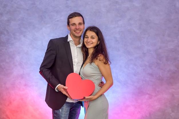 Belle coppie che baciano e che tengono cuore rosso. concetto di san valentino