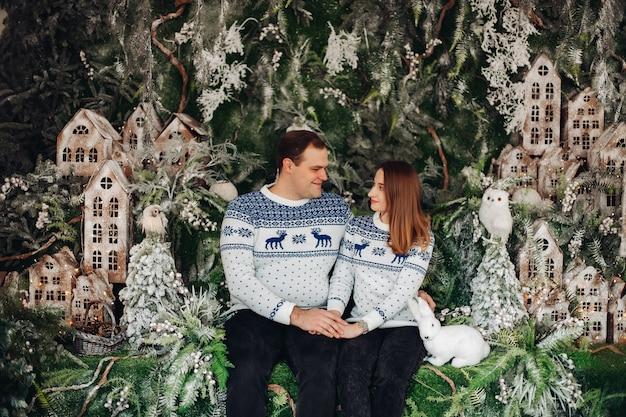 Bella coppia innamorata in maglioni accoglienti con stampa natalizia si siede insieme