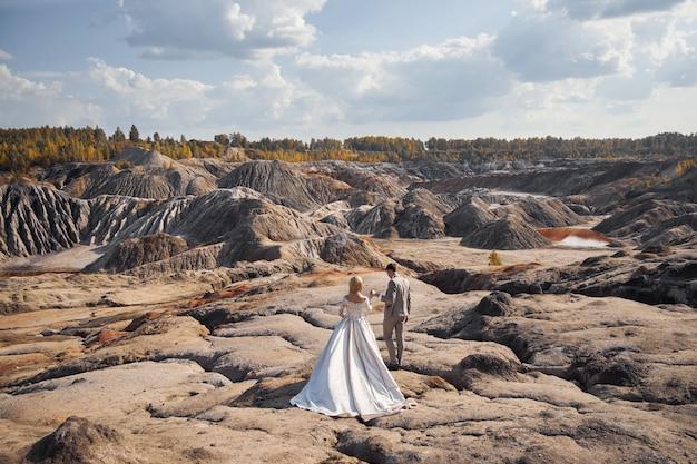 Bella coppia innamorata su un paesaggio favoloso, matrimonio nella natura, amore bacio e abbraccio.