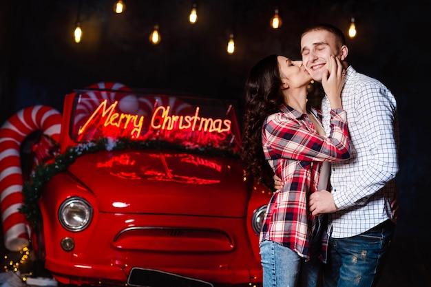 Belle coppie nell'amore che abbracciano sullo sfondo di luci incandescenti e auto retrò