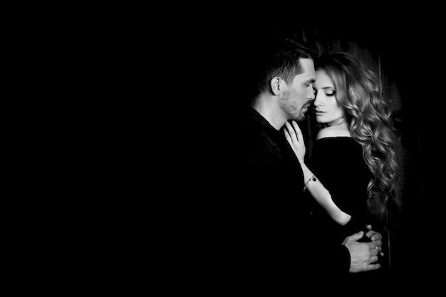 Belle coppie nell'amore che abbraccia sul nero