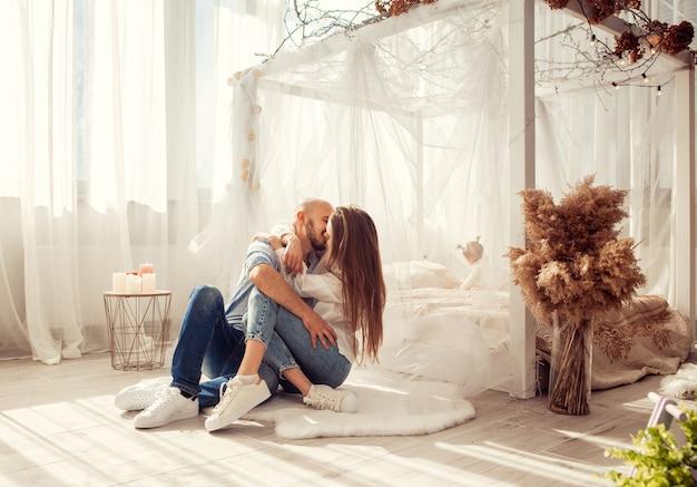 Bella coppia in amore baci e abbracci nella stanza bianca a casa