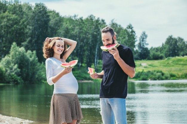 Bella coppia uomo e donna incinta innamorata su uno sfondo