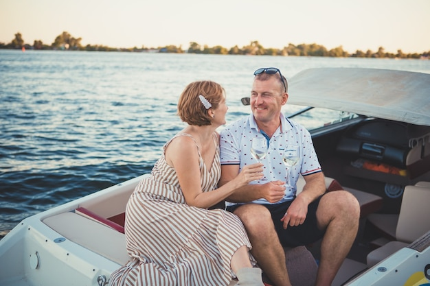 Bella coppia uomo e donna bere vino mentre è seduto in una barca
