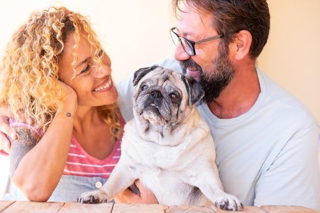 Bella coppia uomo e donna innamorata del loro cane carlino chiaro. per sempre amici