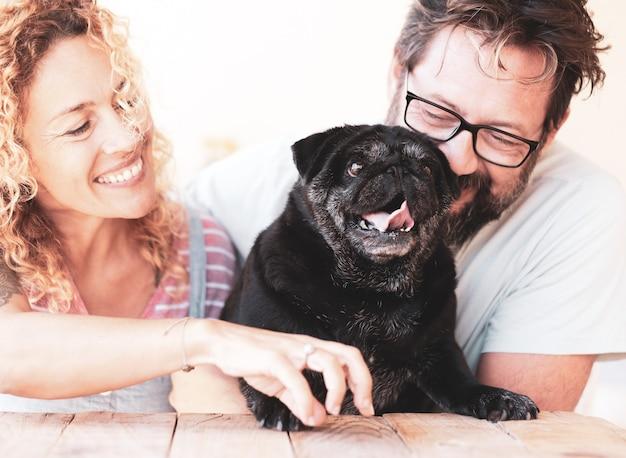 Bella coppia di uomo e donna che sorridono e abbracciano il loro vecchio cane carlino nero all'aperto in terrac
