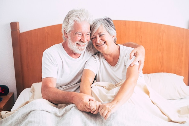 Bella coppia di anziani maturi e pensionati seduti insieme sul letto in camera da letto al mattino - anziani sposati abbracciati dopo il risveglio