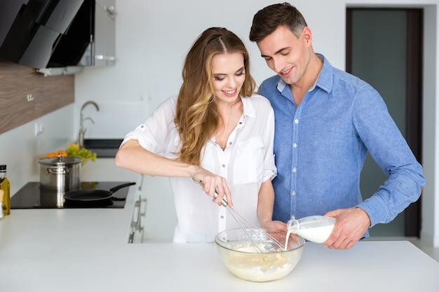 Bella coppia che mescola prodotti in una ciotola di vetro con frullino a mano in cucina