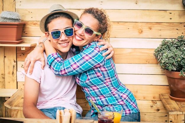 Bella coppia di mamma e figlio insieme abbracciati nella terrazza di casa divertendosi e ridendo - - ragazzo con un cappello felice e divertente