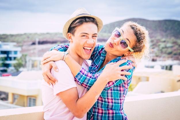 Bella coppia di mamma e figlio insieme abbracciati nel terrazzo di casa divertendosi e ridendo - donna con occhiali da sole e adolescente con una relazione - ragazzo con cappello allegro e divertente