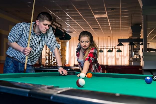 Belle coppie che giocano a biliardo nel pub di notte