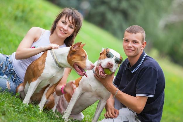 Belle coppie che si siedono sull'erba con i cani
