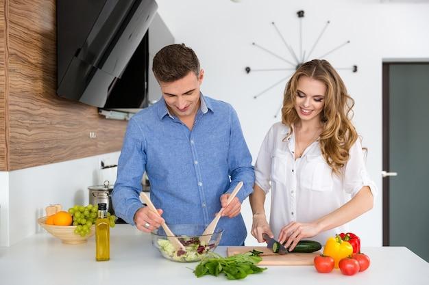Bella coppia in piedi e cucinare cibo sano insieme in cucina