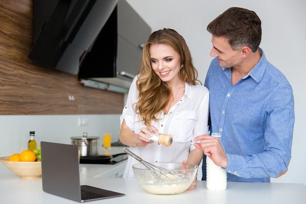 Bella coppia che usa il laptop e cucina insieme in cucina