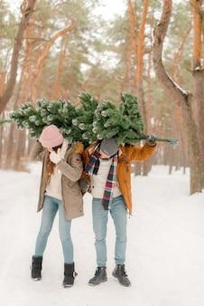 Bella coppia con un albero di natale nel bosco innevato