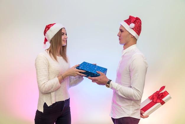 Bella coppia con scatola regalo in posa in cappelli di babbo natale in studio