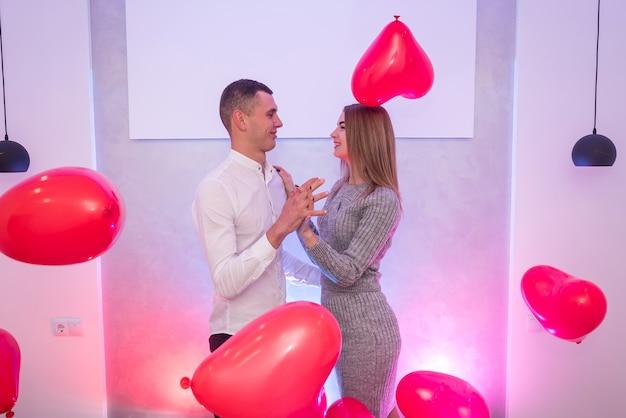 Bella coppia con mongolfiere rosse che celebrano san valentino in posa in studio
