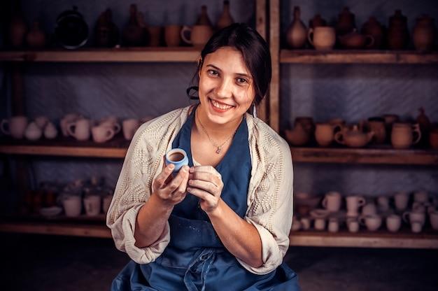 Bellissimo maestro artigiano che modella un vaso di argilla su un tornio da vasaio