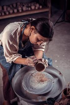 Bellissimo maestro artigiano lavora con l'argilla su un tornio da vasaio