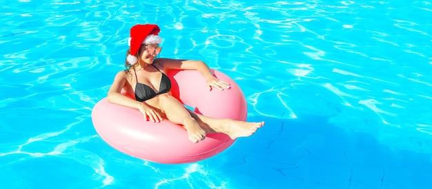 Bella donna pazza in cappello di natale che si rilassa sull'anello gonfiabile in piscina blu. vacanze invernali. copia spazio.