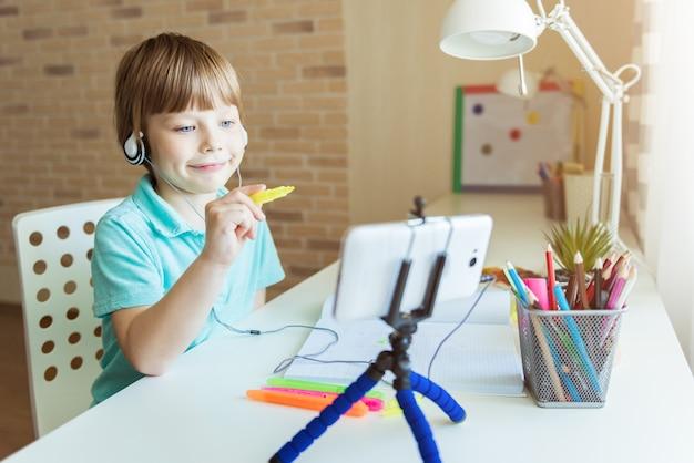 Il bel ragazzo creativo sta seguendo la lezione di disegno online