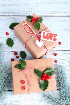 Bellissimi regali di natale con agrifoglio europeo (ilex aquifolium) su tavola di legno