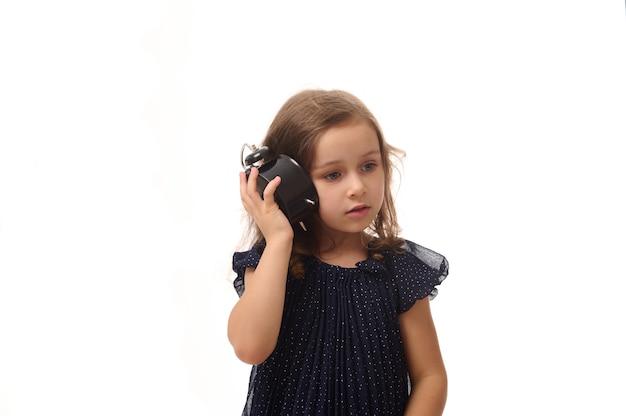 Una bella bambina curiosa di 4 anni in un vestito blu scuro tiene una sveglia vicino al suo orecchio e ascolta attentamente il suono delle frecce, isolata su sfondo bianco con spazio di copia
