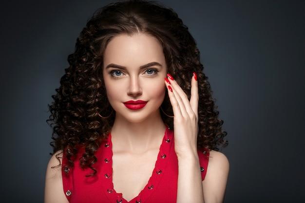 Bei capelli ricci femminili in rosso con labbra rosse e manicure vestito, acconciatura afro rossa di bellezza. colpo dello studio.