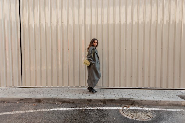 Bella ragazza riccia alla moda in abiti vintage di moda con una borsa cammina vicino a un muro di metallo. lo street style e la bellezza delle donne