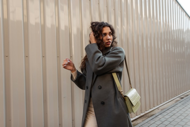 Una bellissima modella riccia con un lungo cappotto verde alla moda con una borsa cammina per strada vicino a un muro di metallo
