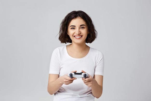 Bella ragazza riccia che gioca con la console di gioco