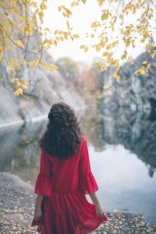 Bella ragazza dai capelli ricci con un vestito rosso al lago che guarda lontano dalla telecamera