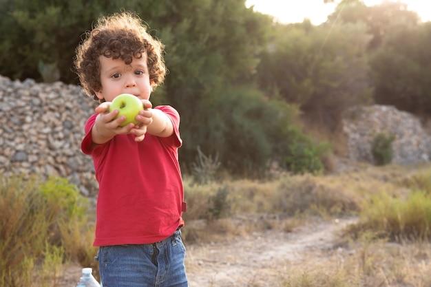 Bellissimo ragazzo dai capelli ricci nel campo e vestito di rosso, che offre una mela gialla